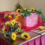 coffin decorated with flowers and sheer fabric